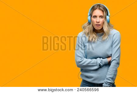 Young beautiful woman listening to music scared in shock, expressing panic and fear