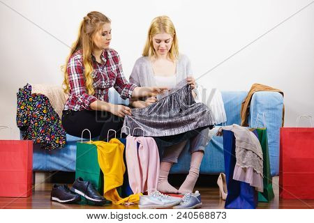 Two Women After Shopping Picking Outfit In Closet. Female Friends Having Doubts About New Clothes