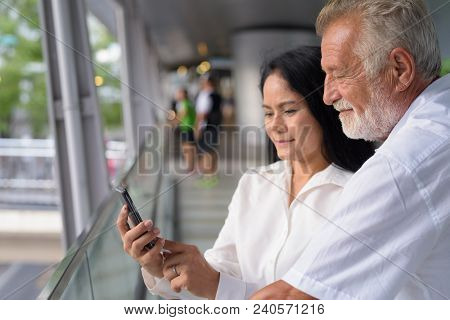 Portrait Of Mature Multi-ethnic Couple On The Footbridge Against View Of The City In Bangkok, Thaila