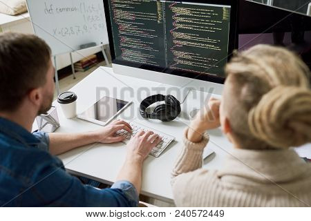 High Angle View Portrait Of Two Contemporary Program Developers Writing Code Sitting At Desk Using C