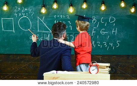 Individual Education Concept. Teacher And Schoolboy Turned Back In Classroom. Kid In Graduation Cap