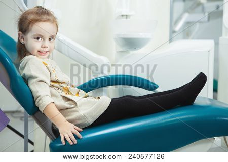 Little Child With Adorable Smile And Big Brown Eyes Sits In Comfortable Leather Dentist Chair In Off