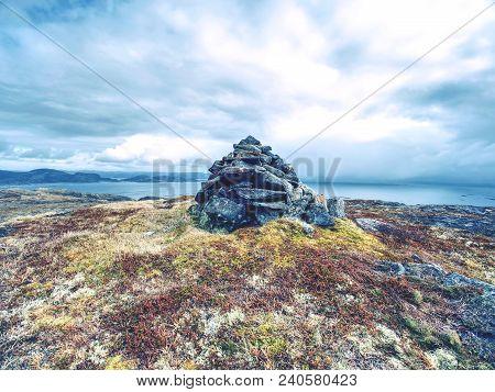 Stones Pyramid On Gravel Mountain Summit. Daybreak Horizon Above Blue Ocean Bellow.  Sea Increased F