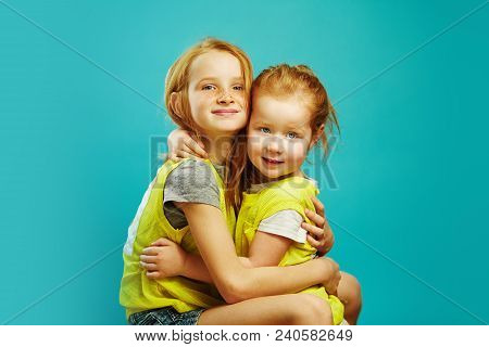 Two Red Haired Child Sister Cute Hugging Isolated On Blue Background. Friendly Relations Between Rel