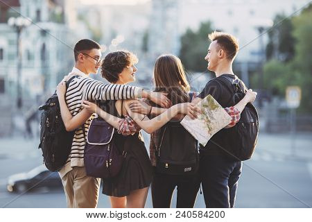 People Travel, Vacation, Holidays, Friendship, City Tour. Friends Travelers With Backpacks Hugging A