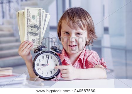 Time To Make Money. Humorous Portrait Of Cute Little Business Child Girl Holding A Clock And Us Doll