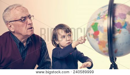Grandfather And Granddaughter Look At The Globe And Teach Geography.