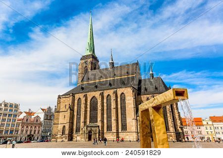 St. Bartholomew's Cathedral In The Main Square Of Plzen With A Fountain On The Foreground Against Bl