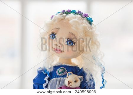Face Portrait Of Textile Handmade Vintage Doll With Blue Eyes, Long Blond Hair In Old Blue Textile D