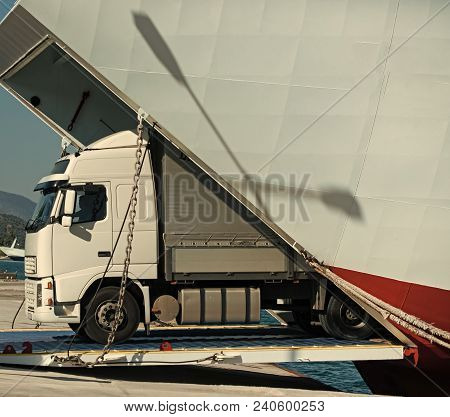 Camion Rides Out Of Ferry, Ferryboat On Sunny Day. Intercontinental Transport. Argo Van, Truck, Kami