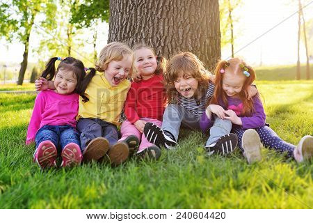 A Group Of Small Children In Colorful Clothes Embracing Sitting On The Grass Under A Tree In A Park