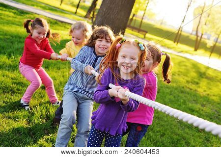A Group Of Small Preschool Children Play A Tug Of War In The Park.