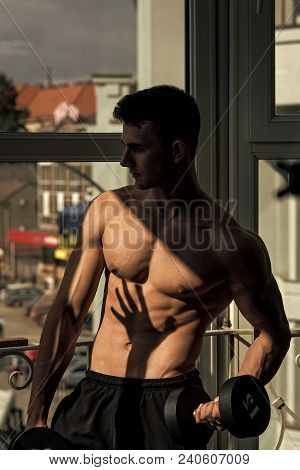 Sportsman, Athlete With Muscles Does Exercises With Dumbbells Near Window. Man With Torso, Muscular