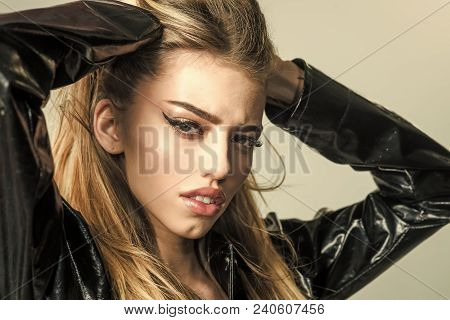 Girl With Long Hair Wears Black Cloak, Grey Background. Lady Sexy In Slicker Or Raincoat Posing, Clo