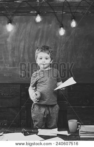 Little Boy Holding Paper Plane And Apple In His Hands. Schoolboy In Blue T-shirt Standing Behind The