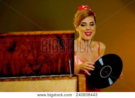 Retro woman with music vinyl record and gramophone. Pin-up retro female style portrait. Girl pin-up style wearing red dress and sitting near player. Retro style is one of most relevant styles.