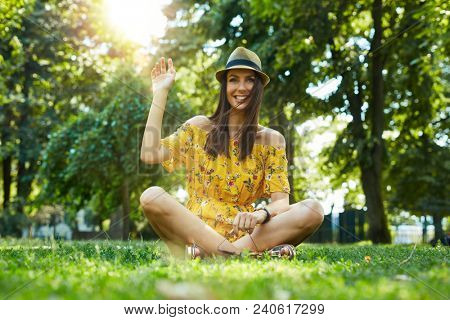 Woman portrait - Happy young woman in the city park outdoor in summer wearing summer dress and trendy hat sitting on grass. Lensflare and vivid colors.