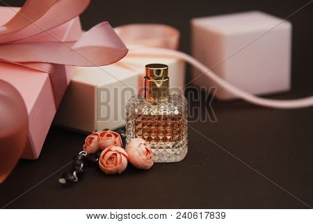 Women's Pink Perfume In Beautiful Bottle And Artificialt Flowers Bracelet On Brown Background With G