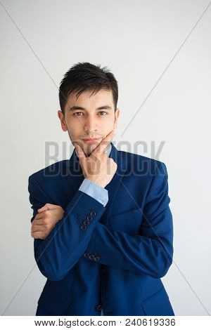 Pensive Young Business Man Touching Chin And Looking At Camera. Contemplation Concept. Isolated Fron