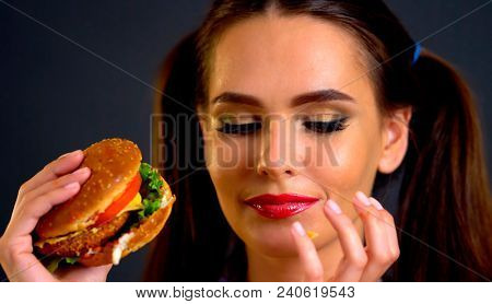 Woman eating hamburger. Girl wants to eat burger. Student consume fast food. Portrait of person with good appetite have greedily dinner delicious sandwich. How to cook in restaurant.