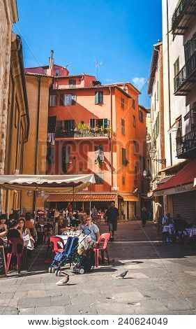 Nice, France - October 13, 2009: People Relaxing In Cosy Street Cafe Among Historic Traditional Hous