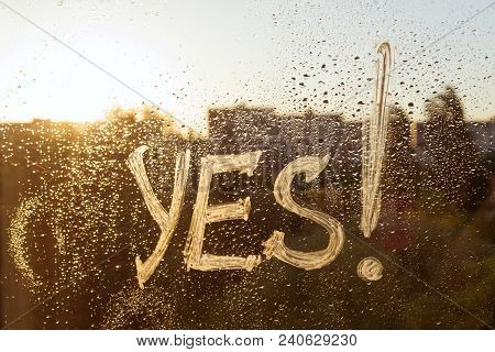 The Word Yes On The Window With Water Drops On Sunny Background, Yes Written With White Toothpaste.