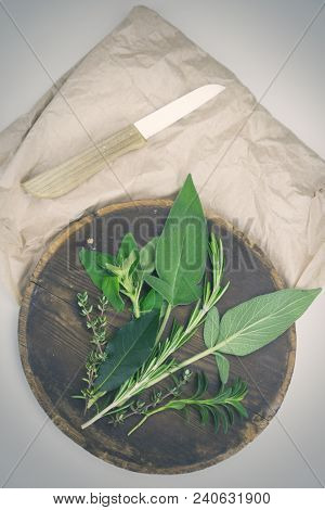 Assorted Fresh Herbs De Provence On A Wooden Chopping Board With A Kitchen Knife And Paper Ready For
