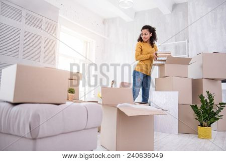 Bye Dorm. Beautiful Curly-haired Girl Packing Books Into The Box While Preparing To Move Out Of The