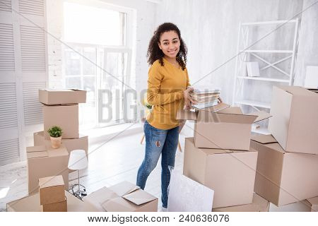 New College Life. Cheerful Young Girl Taking Books Out Of The Box And Smiling At The Camera While Un