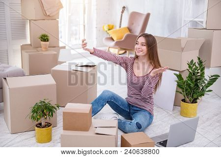 Capturing Moment. Upbeat Young Woman Taking A Selfie And Smiling While Sitting On The Floor And Pack