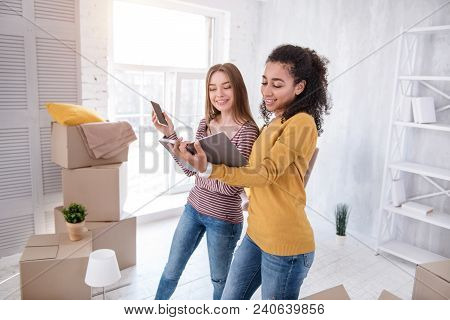 Assistance With Moving. Pleasant Cheerful Girls Checking The Notebook For A Number Of A Removers Com
