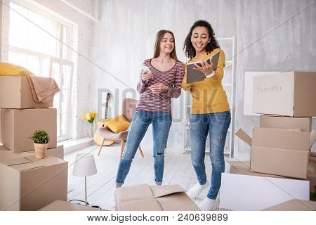 Assistance Needed. Cheerful Young Girls Searching For Phone Number Of Removers, Being In A Need Of A