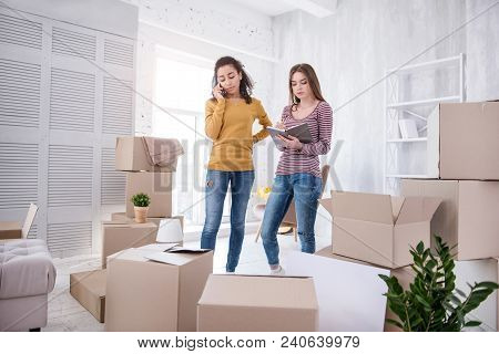 In Need Of Help. Beautiful Young Girls Contacting Removers Company While Finishing Up Packing Their