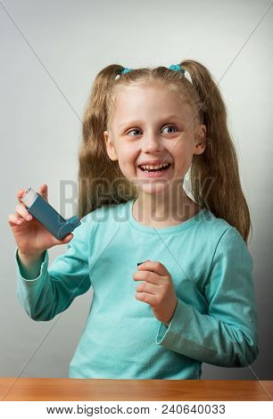 Small Pocket Inhaler For Asthmatics In Hands Of Little Girl On Gray Background