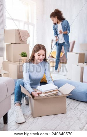 Fruitful Cooperation. Charming Female Student Unpacking A Pile Of Books While Her Roommate Cleaning