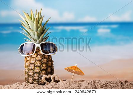 Pineapple With Glasses, Near Little Hearts And An Umbrella On Sandy Coast