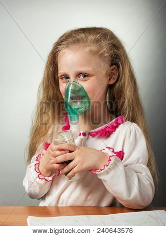 Girl Performs Physiotherapy-inhalation, In The Hands Of Nebulizer With Mask