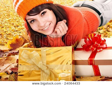 Girl in autumn outdoor holding gift box. Holiday.