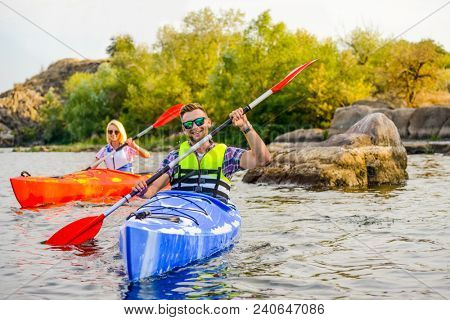 Young Happy Couple Paddling Kayaks on the Beautiful River or Lake