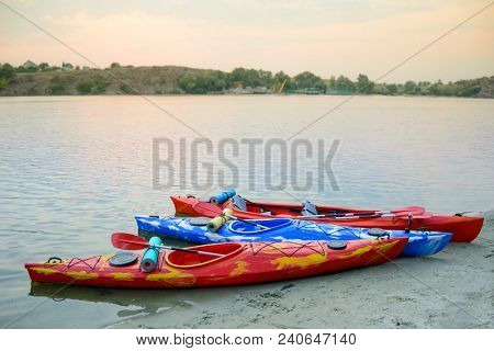 Three Traveling Kayaks on the Sand Beach near Beautiful River or Lake at the Evening. Travel, Adventure and Water Recreation Concept.
