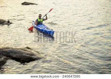 Man Paddling Kayak on the Beautiful River or Lake among Stones at the Evening