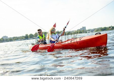 Young Happy Couple Paddling Kayak on the Beautiful River or Lake