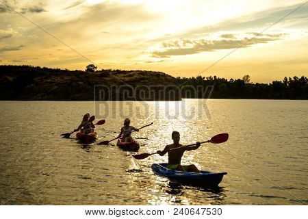 Friends Paddling Kayaks on the Beautiful River or Lake under the Dramatic Evening Sky at Sunset
