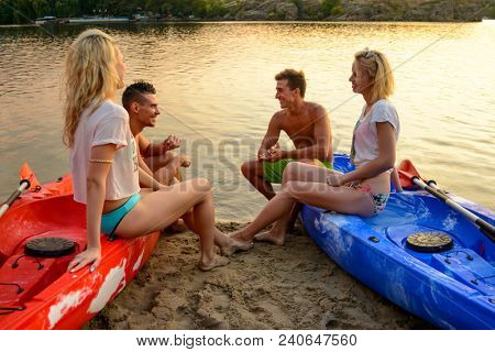 Friends Resting and Talking while Sitting in Kayaks on the River or Lake Beach at Sunset