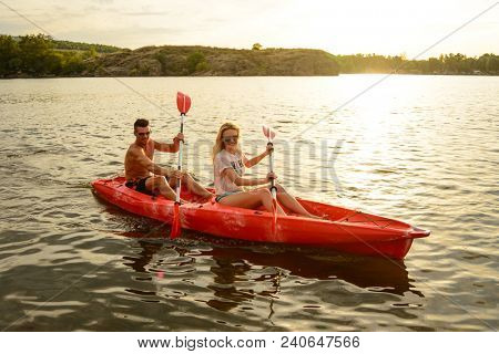 Young Couple Paddling Kayak on the Beautiful River or Lake in the Evening at Sunset