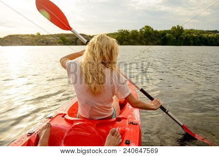 Young Woman Paddling Kayak on the Beautiful River or Lake at Sunset. Back View from the Second Place in the Boat.