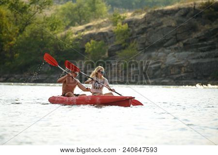 Young Couple Paddling Kayak on the Beautiful River or Lake in the Evening