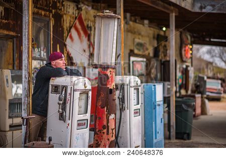 Young Man At A Vintage Gas Pump On Historic Route 66 In Arizona