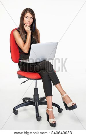 Thinking Contemplating Business Woman Sitting On Office Chair With Laptop Looking At Blank Copy Spac