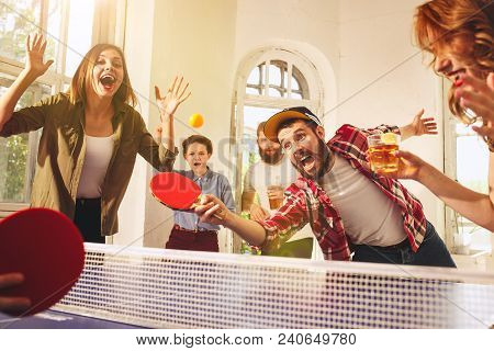 Group Of Happy Young Friends Playing Ping Pong Table Tennis At Office Or Any Room. Concept Of Health